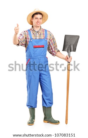 Full length portrait of a male agricultural worker holding a shovel and giving a thumb up isolated on white background - stock photo