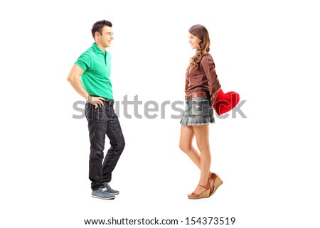 Full length portrait of a male and female with red heart during a date isolated on white background - stock photo