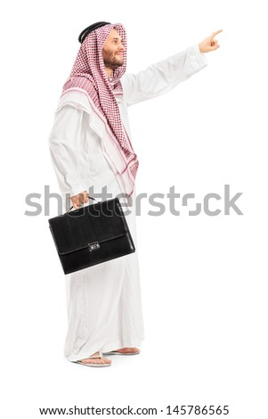 Full length portrait of a male arab person holding a leather suitcase and pointing isolated on white background - stock photo