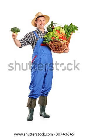 Full length portrait of a male farmer holding a basket full of vegetables isolated on white background