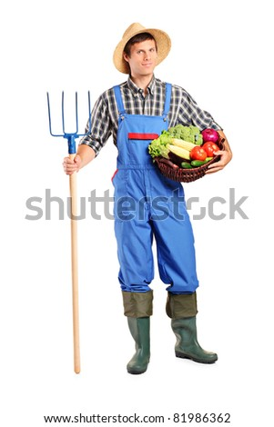 Full length portrait of a male farmer holding a pitchfork and bucket with vegetables isolated on white background - stock photo