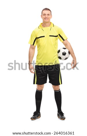 Full length portrait of a male football referee in a yellow jersey holding a ball isolated on white background - stock photo