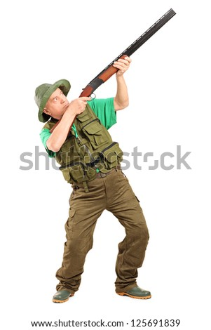 Full length portrait of a male hunter shooting with a shotgun isolated on white background - stock photo