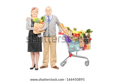 Full length portrait of a man and woman holding a paper bag and shopping cart full of groceries isolated on white background