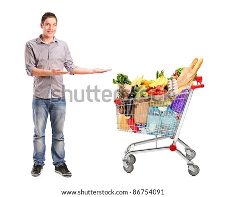 Full length portrait of a man gesturing and shopping cart full with groceries isolated on white background - stock photo