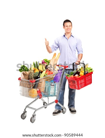 Full length portrait of a man giving thumb up and shopping basket and cart isolated on whte background