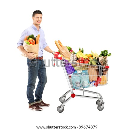 Full length portrait of a man holding a shopping bag and shopping cart isolated on white background - stock photo