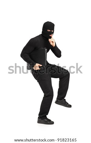 Full length portrait of a man in robbery mask holding a briefcase with finger on the lips gesturing silence isolated on white background - stock photo