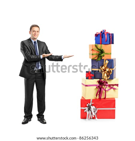 Full length portrait of a man in suit gesturing and pile of gifts isolated on white background - stock photo