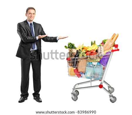 Full length portrait of a man in suit gesturing and shopping cart isolated on white background