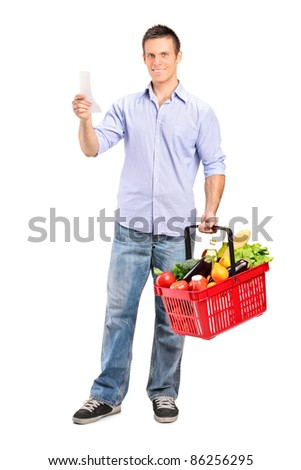 Full length portrait of a man looking at store receipt and holding a shopping basket isolated on white background - stock photo