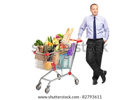 Full length portrait of a man posing next to a shopping cart with groceries isolated on white background