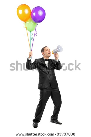 Full length portrait of a man yelling throw a megaphone and holding balloons isolated on white background - stock photo
