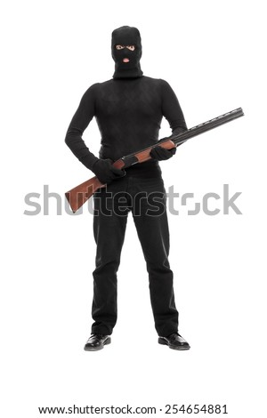 Full length portrait of a masked terrorist holding a shotgun isolated on white background - stock photo