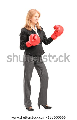 Full length portrait of a mature businesswoman with red boxing gloves ready to fight isolated on white background - stock photo