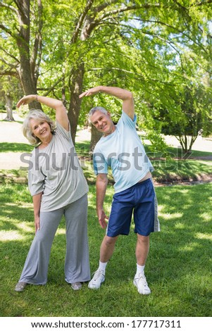 Full length portrait of a mature couple stretching hands at the park
