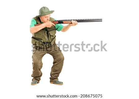 Full length portrait of a mature hunter aiming at something with a gun isolated on white background - stock photo