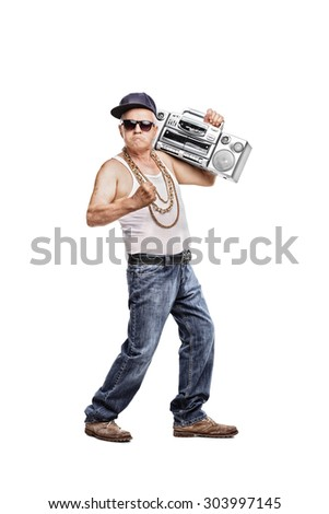 Full length portrait of a mature man in hip-hop outfit holding a ghetto blaster and looking at the camera isolated on white background - stock photo
