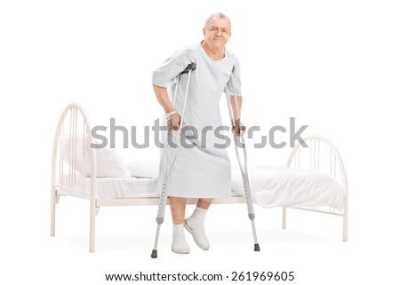 Full length portrait of a mature patient with crutches getting out of bed isolated on white background - stock photo