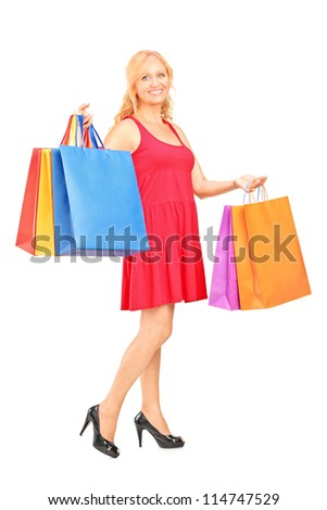 Full length portrait of a mature woman holding shopping bags isolated on white background