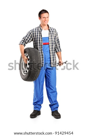 Full length portrait of a mechanic holding a spare tire and holding a wrench isolated on white background - stock photo