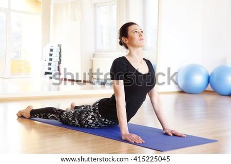 Full length portrait of a middle age woman doing cobra pose on an exercise mat at yoga studio.