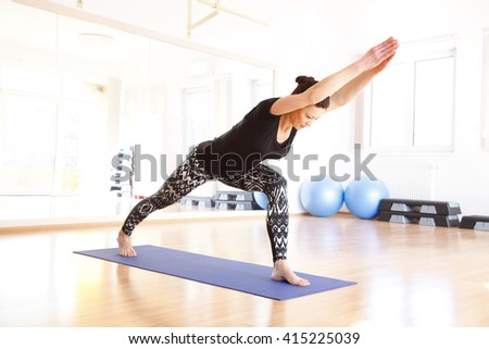 Full length portrait of a middle age woman doing yoga on an exercise mat at yoga studio. - stock photo