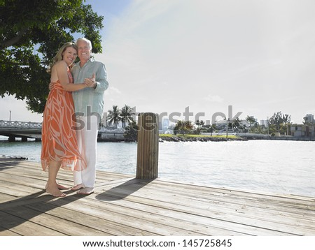 Full length portrait of a middle aged couple embracing on pier - stock photo