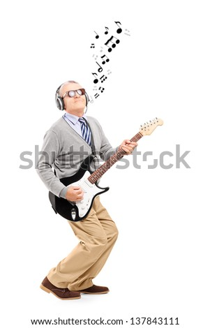 Full length portrait of a middle aged man playing guitar and musical notes around, isolated on white background - stock photo
