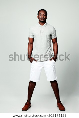 Full length portrait of a pensive african man on gray background - stock photo