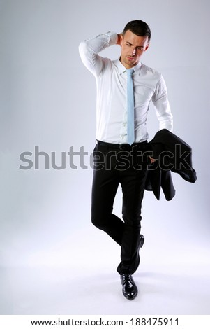 Full length portrait of a pensive business man holding jacket on gray background - stock photo