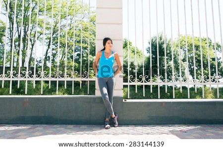 Full length portrait of a pensive sporty woman leaning on the fence outdoors - stock photo
