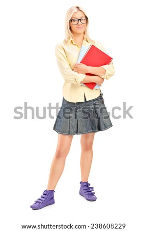 Full length portrait of a pretty female student holding books isolated on white background