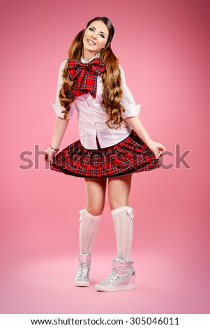 Full length portrait of a pretty smiling teen girl in school uniform posing over pink background. Anime style.  - stock photo