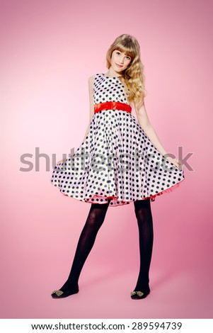 Full length portrait of a pretty teenager girl posing in pin-up dress over pink background.  - stock photo