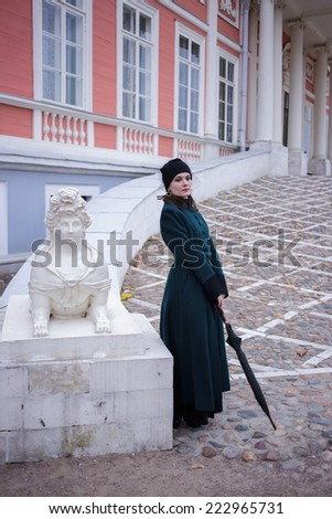 Full-length portrait of a pretty woman in vintage autumn clothes standing in front of old city buildings