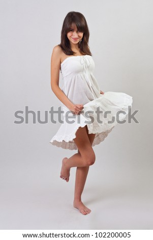 Full length portrait of a pretty young girl wearing a nice summer dress and dancing - stock photo