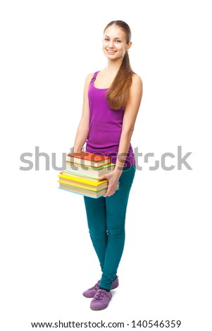 Full length portrait of a pretty young happy smiling student girl holding stack of books isolated on white background - stock photo
