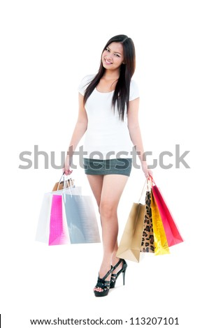 Full-length portrait of a pretty young woman holding shopping bags over white background.