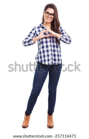 Full length portrait of a pretty young woman making a heart sign with her hands - stock photo