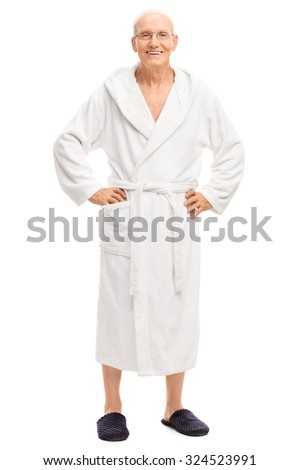 Full length portrait of a relaxed senior man in a white bathrobe smiling and looking at the camera isolated on white background - stock photo