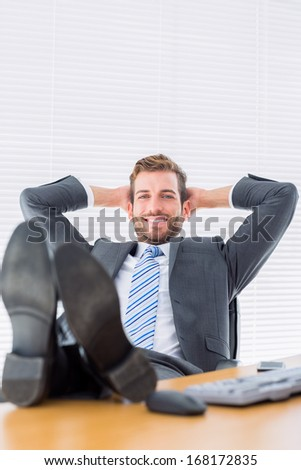 Full length portrait of a relaxed young businessman sitting with legs on desk at office