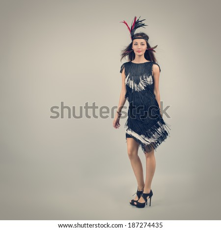 Full Length Portrait of a Retro Fashion Woman on Gray Background. 20s Vintage Style. Toned Photo. Copy Space. - stock photo