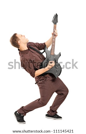Full length portrait of a rock star playing guitar isolated on white - stock photo