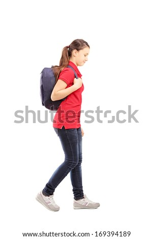Full length portrait of a sad schoolgirl with a bag walking, isolated on white background - stock photo