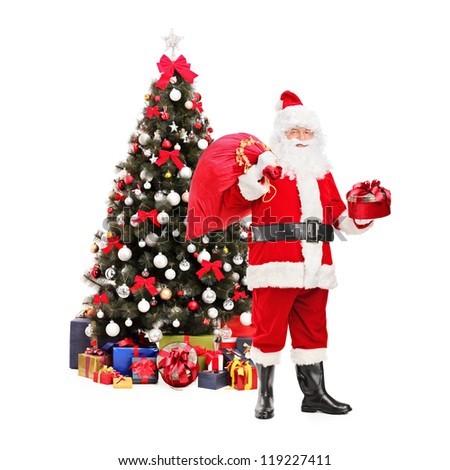Full length portrait of a Santa Claus holding a bag and standing next to a Christmas tree isolated on white background - stock photo