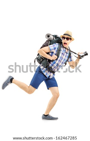 Full length portrait of a scared hiker with backpack and camera running away isolated on white background - stock photo