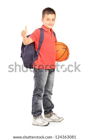 Full length portrait of a school boy with backpack holding a basketball and giving a thumb up isolated on white background