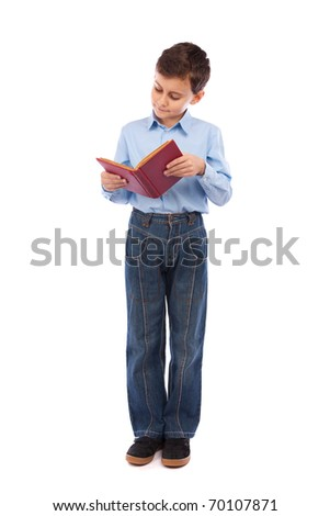 Full length portrait of a schoolboy reading a book - stock photo