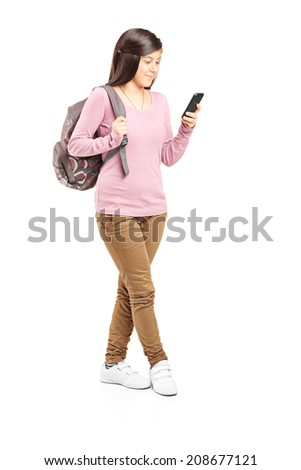 Full length portrait of a schoolgirl looking at her cell phone isolated on white background - stock photo